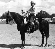 Black and white photo of a man riding a horse